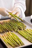 Hands with fresh asparagus in kitchen