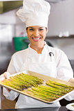 Smiling chef holding tray of fresh asparagus in kitchen