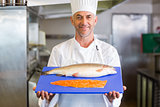 Confidence chef holding tray of raw fish in kitchen