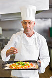 Confident chef holding cooked food in kitchen
