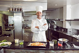 Confident male chef with cooked food in kitchen