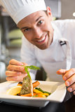 Smiling male chef garnishing food in kitchen