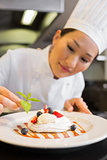 Concentrated female chef garnishing food