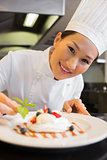 Closeup of a smiling chef garnishing food