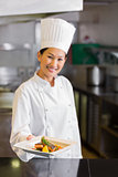 Confident female chef holding cooked food in kitchen