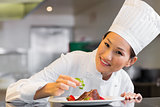 Smiling female chef garnishing food in kitchen