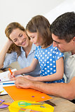 Parents looking at daughter coloring