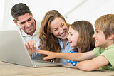 Cheerful family using laptop