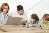 Mother using laptop while father assisting children in coloring