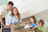 Children coloring while parents using laptop