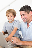 Father reaching son to use laptop