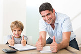 Father and son gesturing thumbs up while doing homework