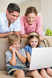 Parents watching children using laptop
