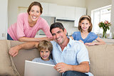 Smiling family using laptop in sitting room