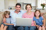 Family with laptop sitting on sofa