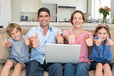 Family with laptop gesturing thumbs up on sofa