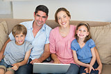 Parents and children with laptop on sofa