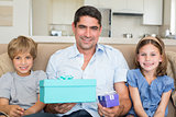 Father holding gifts by children on sofa