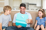 Father opening gift given by children on sofa