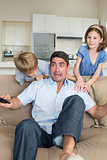 Children scaring father watching television