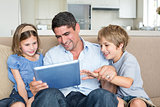Father and children using digital tablet