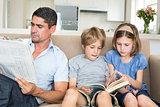 Father with newspaper while children reading book
