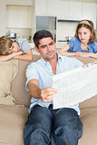 Bored children looking at father reading newspaper
