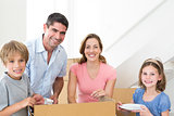 Happy family unpacking cardboard box in house