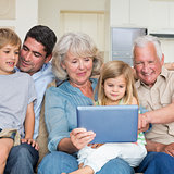 Smiling family using digital tablet