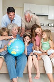 Family exploring globe in living room