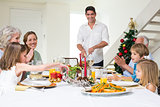 Family enjoying Christmas meal at dining table