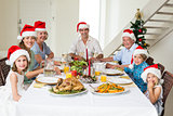 Happy family in Santa hats having Christmas meal