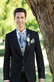 Confident groom smiling at garden
