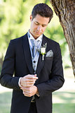 Groom adjusting sleeve at garden