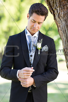 Groom adjusting sleeve at garden