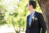 Groom looking away in garden