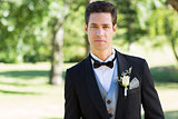 Confident groom in tuxedo at garden