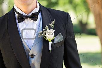 Bridegroom wearing boutonniere in garden