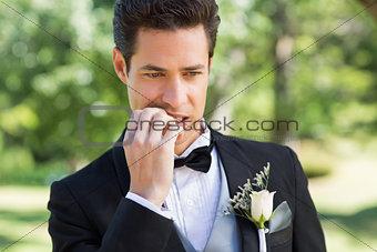 Groom biting nails in garden