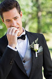 Young groom biting nails in garden