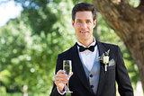Groom holding champagne flute in garden