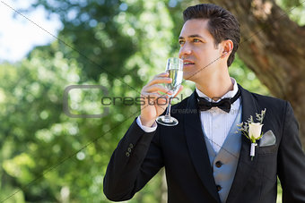 Thoughtful groom drinking champagne