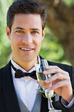 Handsome groom drinking champagne in garden