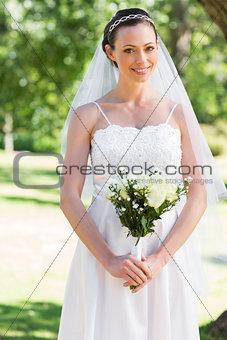 Bride holding bouquet in park