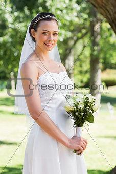 Bride holding flowers in garden