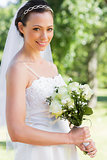 Confident bride holding flower bouquet in garden