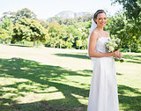 Happy bride holding flower bouquet in garden