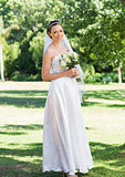 Portrait of bride holding flower bouquet in garden