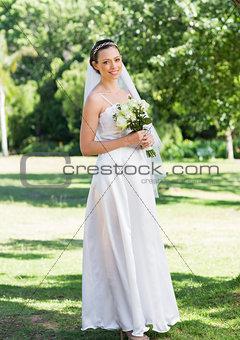 Portrait of bride holding flower bouquet in garden