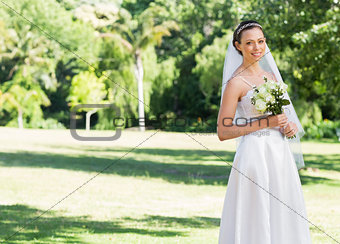 Attractive bride holding flowers in park